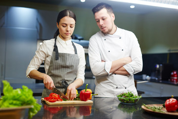Professional chef and his trainee cooking fresh vegetable salad