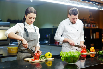 Young man and woman cutting vegetables in the kitchen