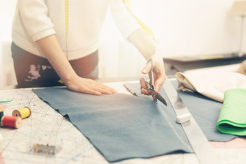 tailoring workshop - woman tailor cutting fabric with scissors