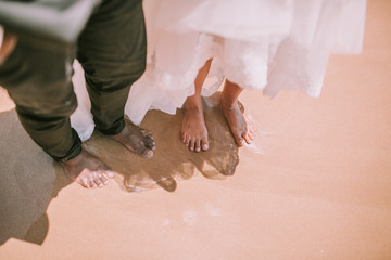 bride groom barefoot on the beach