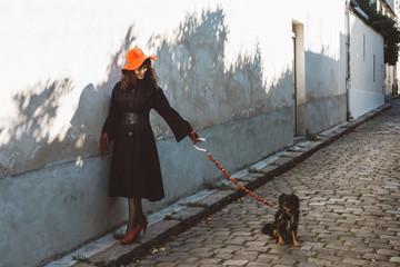 Dame au chapeau rouge avec son chien dans la rue