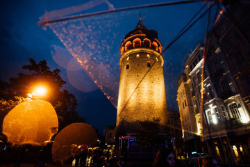 Istanbul, Galata Tower. View on architecture through a transparent umbrella in the rain. Nice bokeh. Tourism