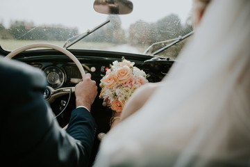 Bride and groom driving car