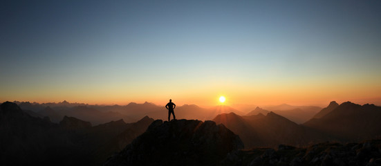 Man reaching summit enjoying freedom and looking towards mountains sunset.