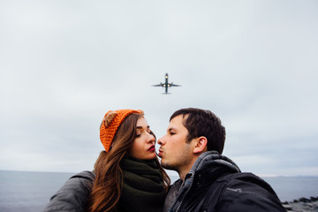 A guy and a girl, the couple embraced doing selfie standing in a picturesque place rocks. Against the background of a plane flies overhead. Autumn sky. Brunette long hair, knitted bandage.
