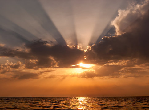 Beautiful scenic sunset seascape with sun peeping out from behind the cloud generating radiating sunrays and reflecting from the calm sea water surface