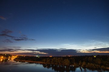 Beautiful night starry landscape. Astrophotography. Clear starry sky. Slow shutter speed. The spectacular sky. Scenic view. Water surface. Noctilucent clouds.