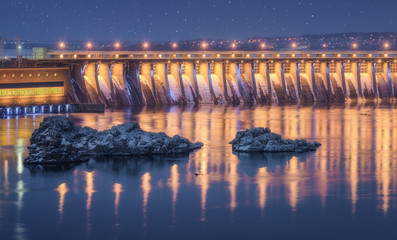 Barrage Dam. Beautiful night industrial landscape with dam hydroelectric power station, bridge, river, city illumination reflected in water, rocks and blue starry sky in winter in Ukraine. Cityscape