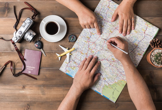 Young couple planning  vacation trip with map. Top view.