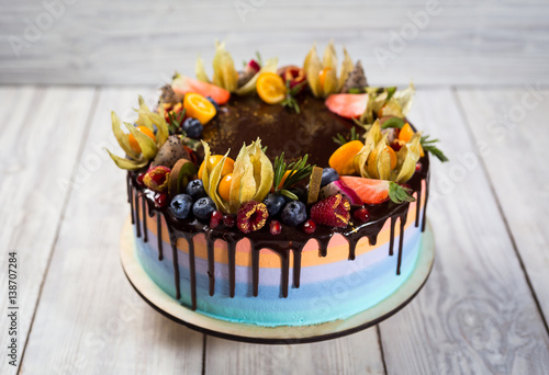 Chocolate cupcakes with colored layers decorated with fruit