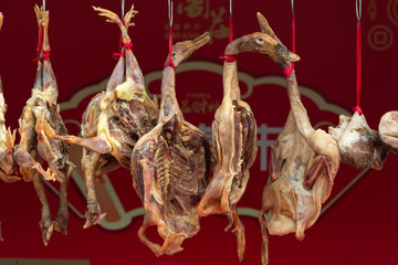 Freshly gutted ducks hanging in an open market with a shallow depth of field