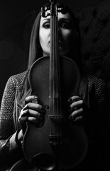 Girl holds a violin in hands. Black and white photo