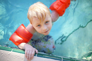 Cute Young Child with Arm Floaties in Swimming Pool