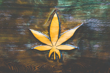 Marijuana leaf artfully crafted and carved on a piece of wood with visible wood grain with slight psychedelic colors.