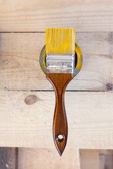 Bank with yellow paint and a brush, top view. Brush with wooden handle closeup