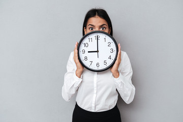 Young Business woman hiding behind the clock