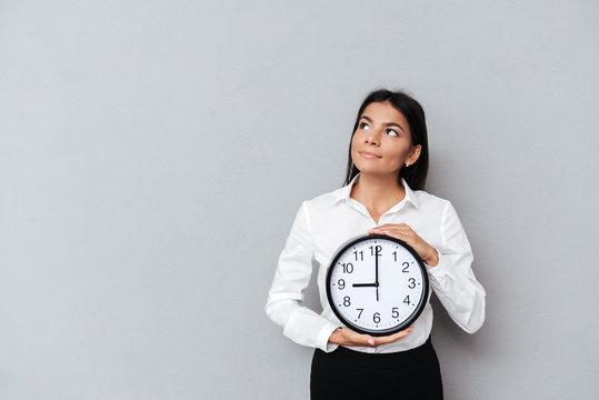 Business woman holding clock and looking up