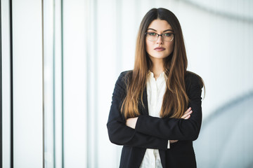 Smiling young Business woman crossed arms, standing against office
