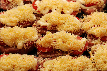 Raw fresh meat sliced with cheese, tomato sauce and spices on a baking tray, ready to be placed in the oven.
