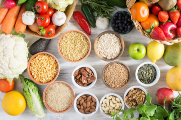 Variety of fruits and vegetables, cereals, nuts on the white wooden table, top view, copy space for text, selecitve focus. Basket of strawberries, apples, oranges, kiwi, bowls of oats, spelt, rice