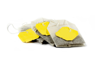 Three (3) isolated tea bags isolated on a pure white background with yellow tags.