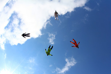 Skydivers are flying in the blue sky