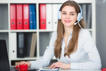 Student woman uses a headset with a microphone for online learning university,looks into the camera.