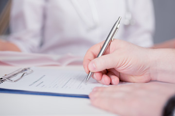 The patient completes the questionnaire in a doctor's office. Pen in hand. The image depth of field.