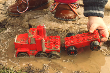 A child playing with a red car in the mud puddle.