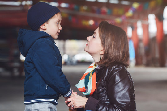 Portrait of white Caucasian mother and son talking to each other, happy family of two, lifestyle outside on a spring autumn day