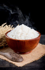 Cooked rice with smoke in wooden bowl,dark background