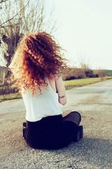 Chica adolescente pelirroja de espaldas a la cámara sentada frente a una carretera que se extiende lejos