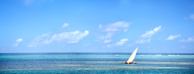Wall Mural - Panoramic view of ocean waters with traditional dhow boat in Zanzibar