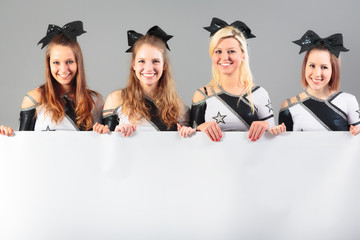 Group Of Cheerleaders Holding White Poster