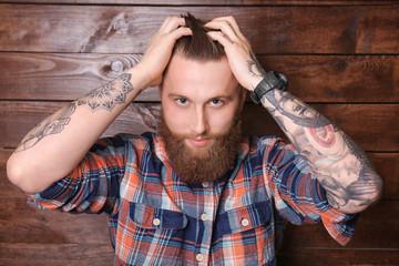 Bearded man posing on wooden background
