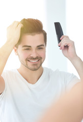 Handsome young man combing hair while standing in front of mirror