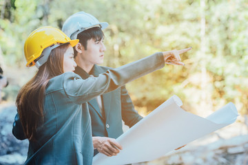 asian  engineer hand holding blueprint working in area forest