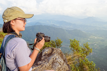 Hiker asian teen girl wear cap and eyeglass with happy holding dslr camera for photography beautiful natural in winter on peak mountain at Phu Chi Fa Forest Park, Chiang Rai, Thailand