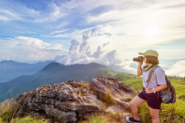 Hiker asian teen girl wear cap and eyeglass with happy holding dslr camera shooting photo beautiful nature in winter on peak mountain at sunset in Phu Chi Fa Forest Park, Chiang Rai, Thailand
