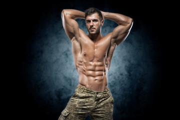 Muscular young man in studio on dark background Wall mural