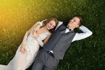Wedding toned photo, happy couple lying on green grass. Bride and groom embracing and dreaming about honeymoon. Rustic wedding