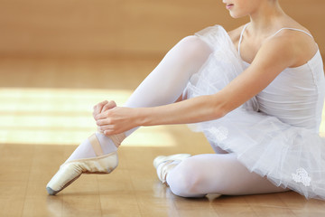 Young beautiful ballerina tying point shoes on floor