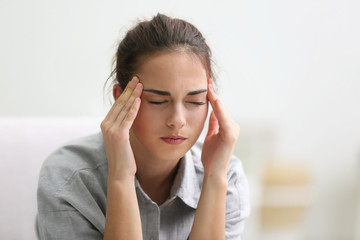 Portrait of young woman suffering from headache at home