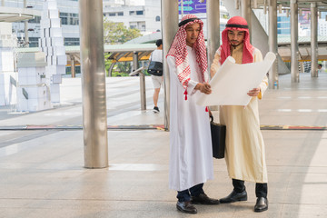 Two Arab businessmen are looking at blueprints with in the city.