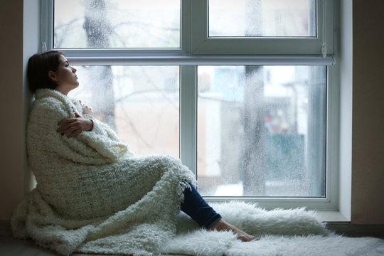 Depressed young woman sitting on window sill indoors