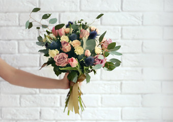 Female hand holding beautiful bouquet on brick wall background Fototapete