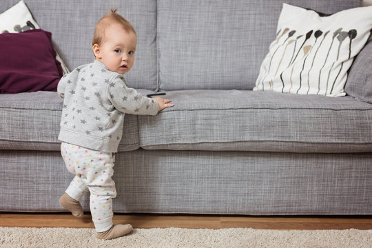 Eleven months old baby girl standing by the sofa, holding it with her tiny hands