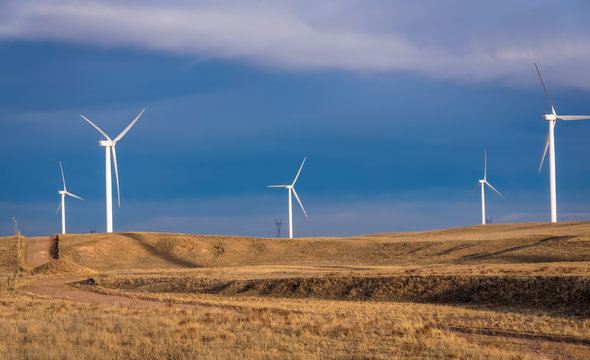 Wind turbine farm in a yellow field, meadow, on a bright blue sky background with clouds. Landscape of a wind farm. USA
