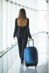 Portrait of an attractive young business woman walking with baggage before boarding on plane