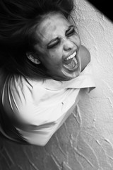 screaming crazy young woman in straitjacket, monochrome